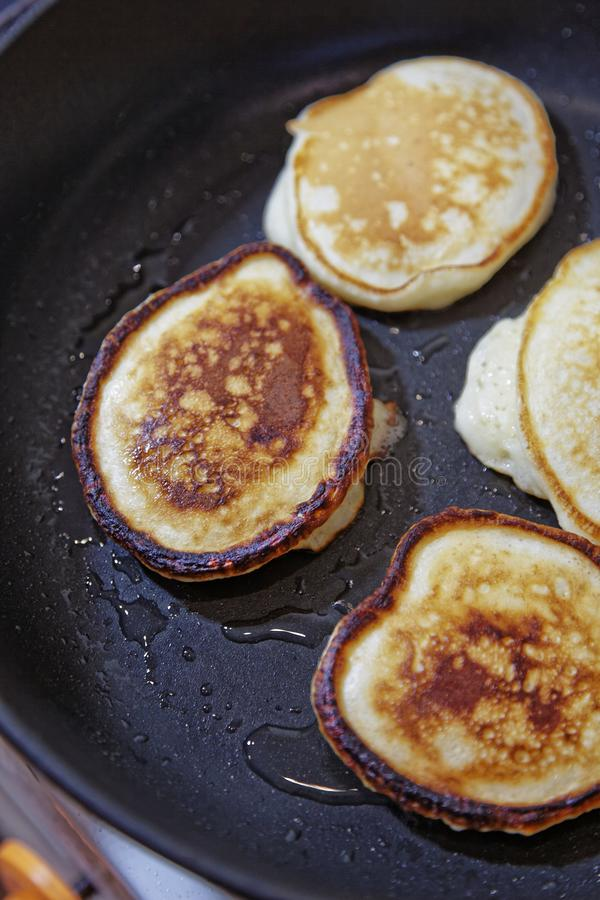 Sweet pancakes are fried in a frying pan. Home kitchen. Preparation of homemade food. royalty free stock photo
