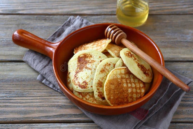 Sweet pancakes with honey on a ceramic pan royalty free stock photos