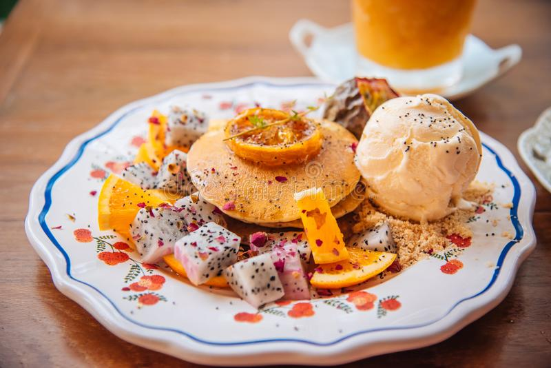 Sweet Pancakes with honey and vanilla ice cream Fruit with Orange focus on pancake stock image