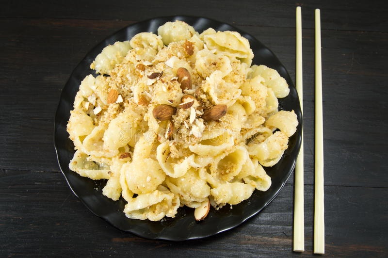 Sweet pasta with nuts and almonds on a plate. With chopsticks royalty free stock image