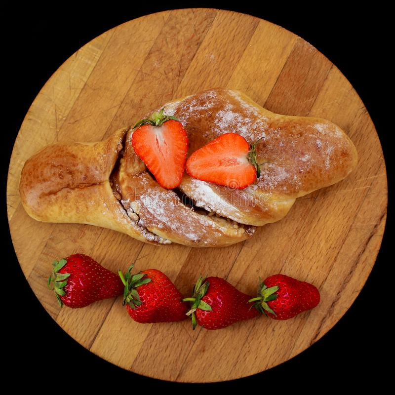Sweet pastry and fresh strawberries on a wooden board. fresh strawberries separately. Black background stock photo