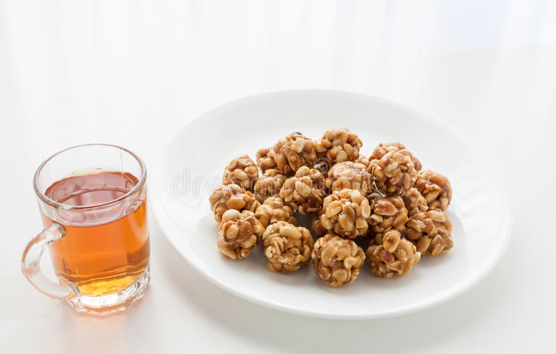Sweet peanut balls in a plate and glass of black tea. On a table with natural light from window stock photography