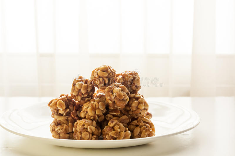 Sweet peanut balls in a plate. On a table with natural light from window stock images