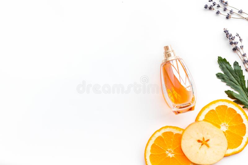 Sweet perfume with fruit fragrance. Bottle of perfume near apple, orange, lavender on white background top view spac. Sweet perfume with fruit fragrance. Bottle stock image