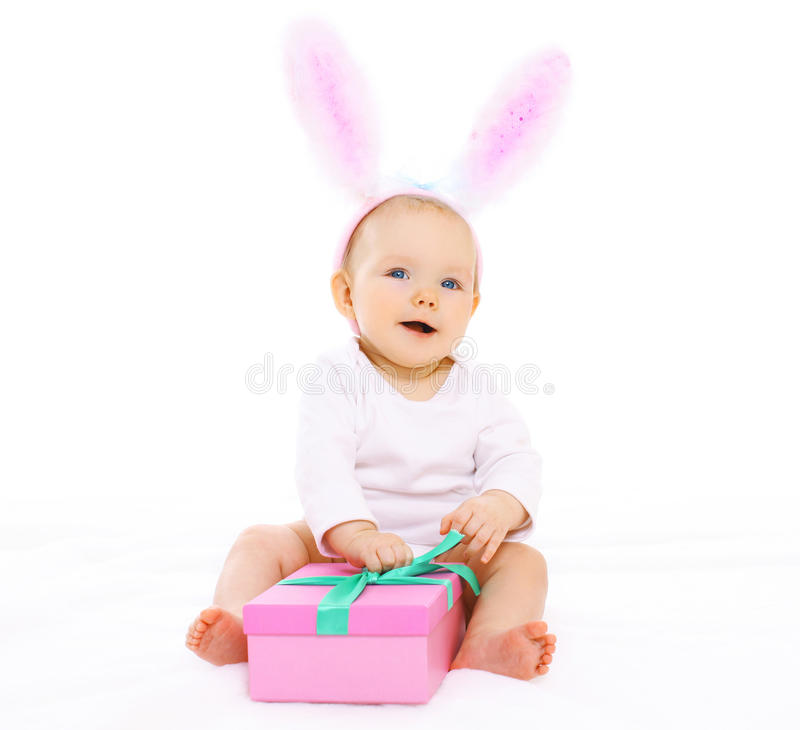 Sweet pink baby sitting in costume easter bunny with fluffy ears. And gift box stock images