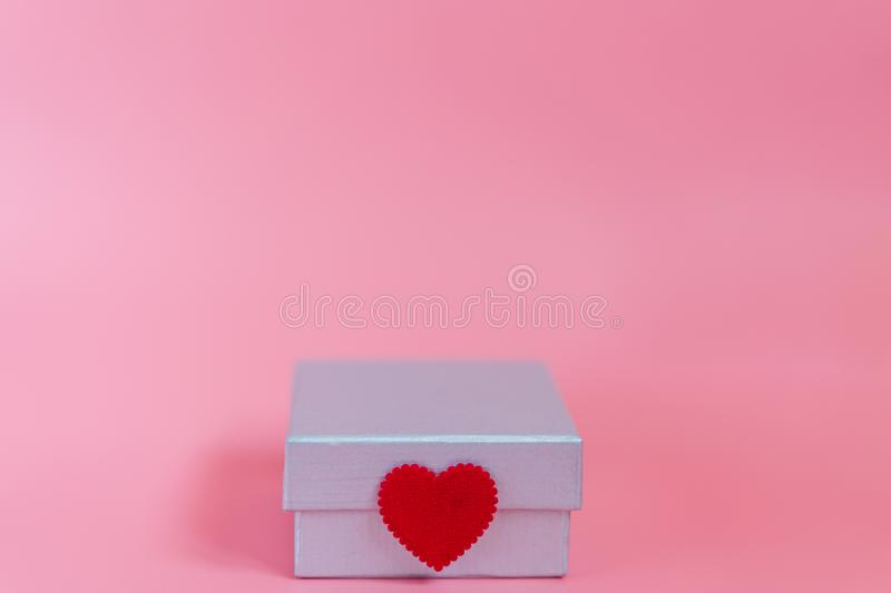Sweet pink background with a silver gift box and decoration seal with a craft little red heart symbol of love and care. Valentines stock photos