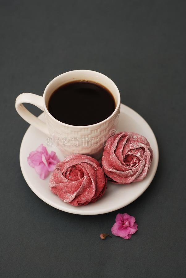 Sweet Pink Meringues and Cup of Coffee on Blue Gray background with Pink Flowers. Spring Background with copy space. Breakfast. stock photography