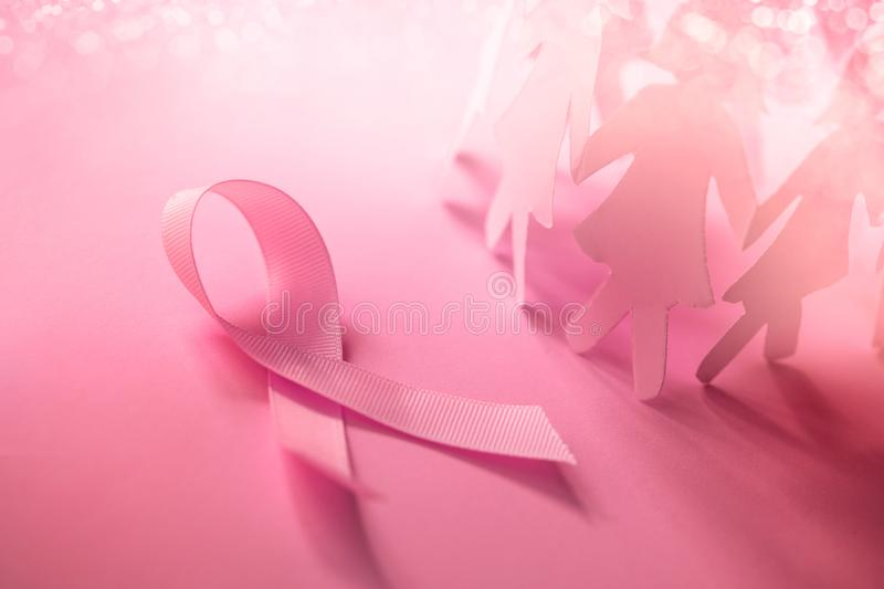 The Sweet pink ribbon shape with girl paper doll on pink background for Breast Cancer Awareness symbol to promote in october mo stock images