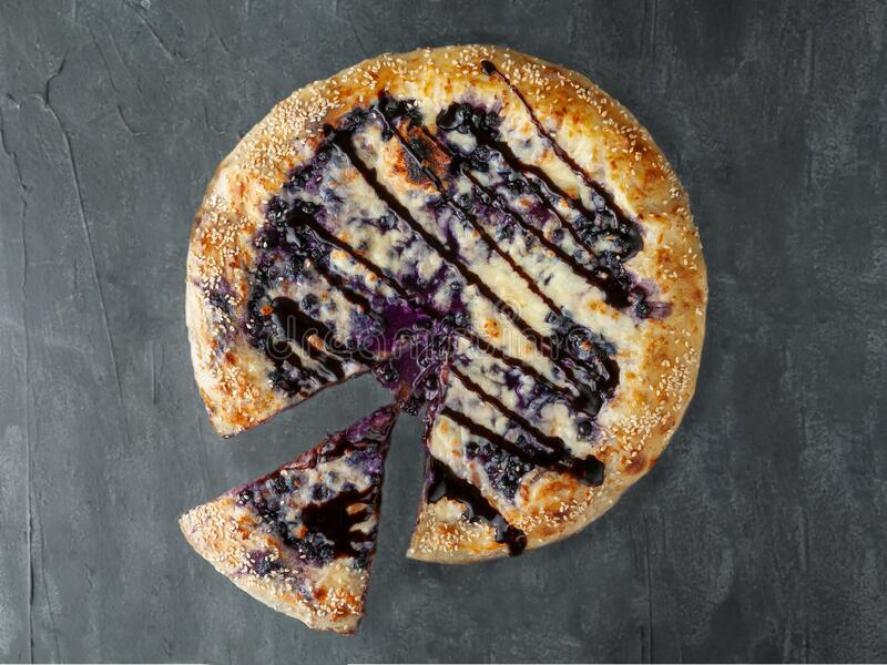 Sweet pizza. blueberries, cream cheese, mozzarella and sulguni, poured with chocolate topping. A piece is cut off from pizza. View stock photo