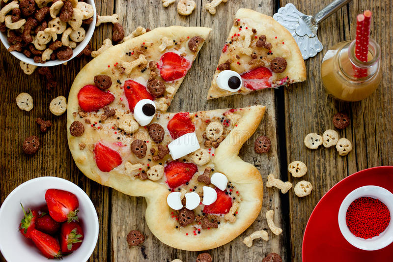 Sweet pizza in the form of funny skull to treat kids for Halloween stock photos
