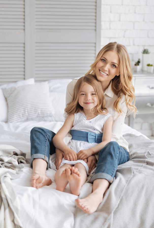Sweet pleasant single-parent family bonding on bed stock photography