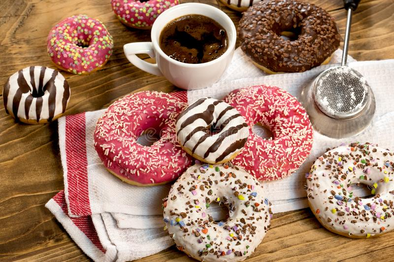 Sweet pleasure for your taste - American donut and cup of coffe. On rustic table royalty free stock photo