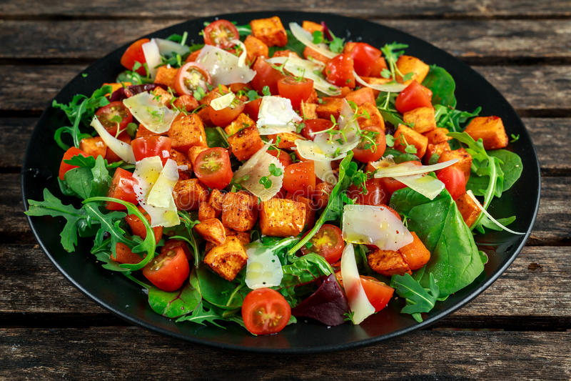 Sweet potato, carrots, cherry tomatoes and wild rocket salad with feta cheese served in black plate royalty free stock images