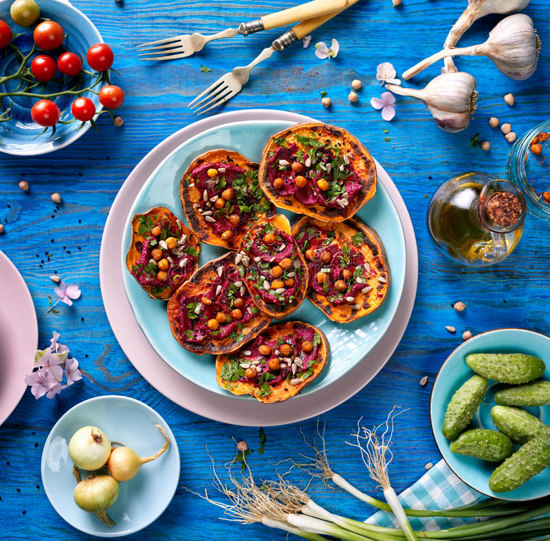 Sweet potato toast with beet hummus, grilled chickpeas, fresh parsley, nigella seeds and sunflower seeds on a plate on a blue ta royalty free stock image
