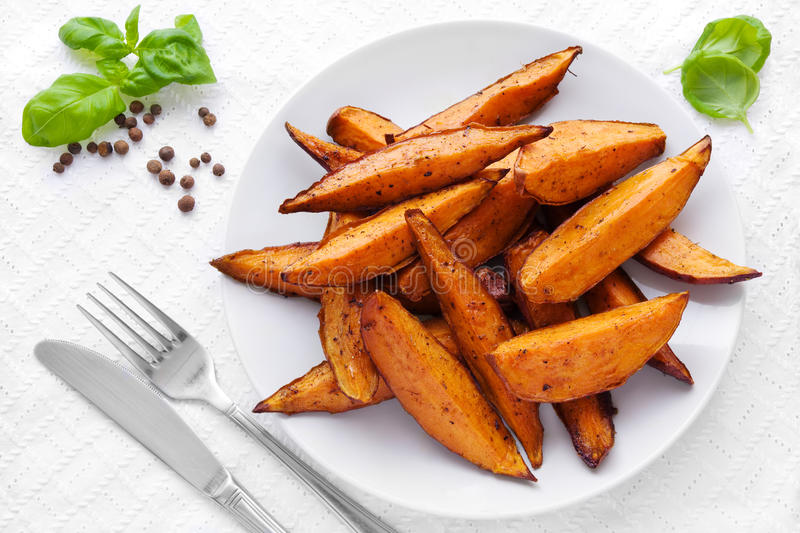 Sweet potato wedges. Delicious homemade sweet potato wedges on a plate royalty free stock photos