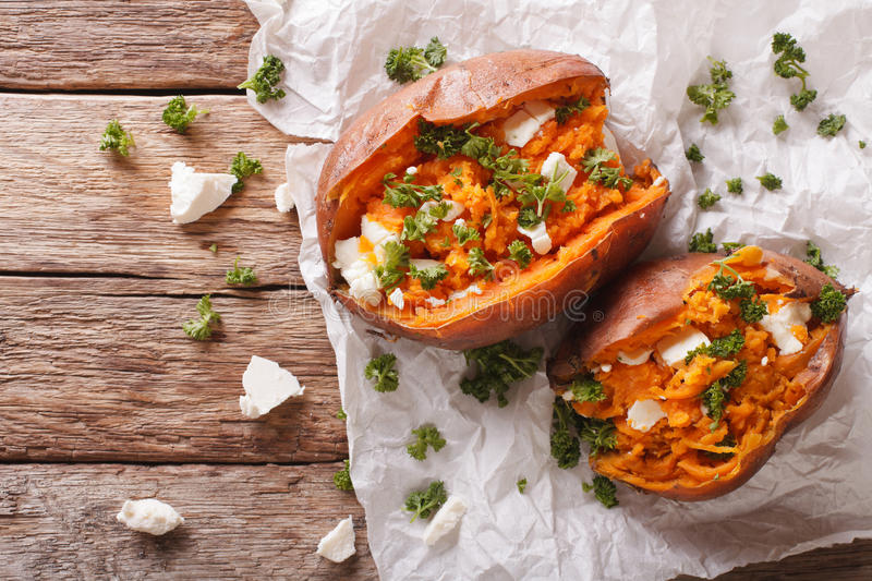 Sweet potatoes baked with feta cheese and parsley on the table. stock image