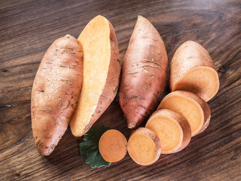 Sweet potatoes on the old wooden table. royalty free stock photos