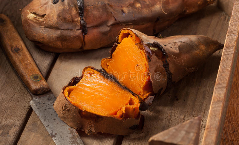 Sweet potatoes. Oven baked sweet potatoes on vintage wood royalty free stock photography