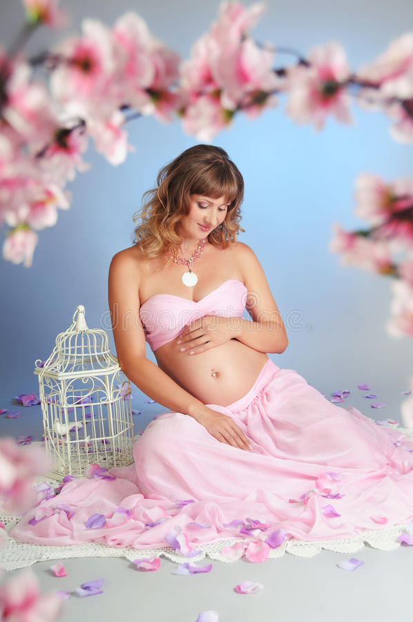 Sweet pregnancy. Beautiful pregnant woman surrounded by flowers royalty free stock photography
