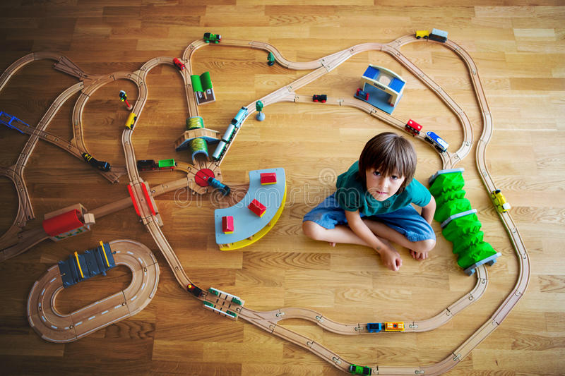 Sweet preschool child, playing with wooden railway and trains at. Sweet preschool child, boy, playing with wooden railway and trains at home, top view stock images