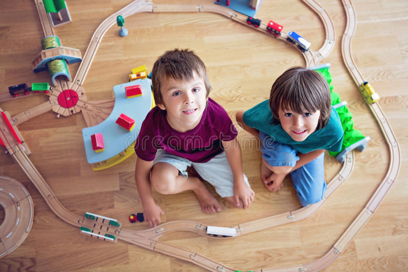 Sweet preschool children, boy brothers, playing with wooden rail stock photos