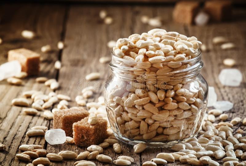 Sweet puffed rice with caramel in a glass jar on the old wooden stock photography