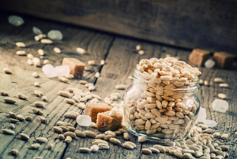Sweet puffed rice with caramel in a glass jar on the old wooden royalty free stock image
