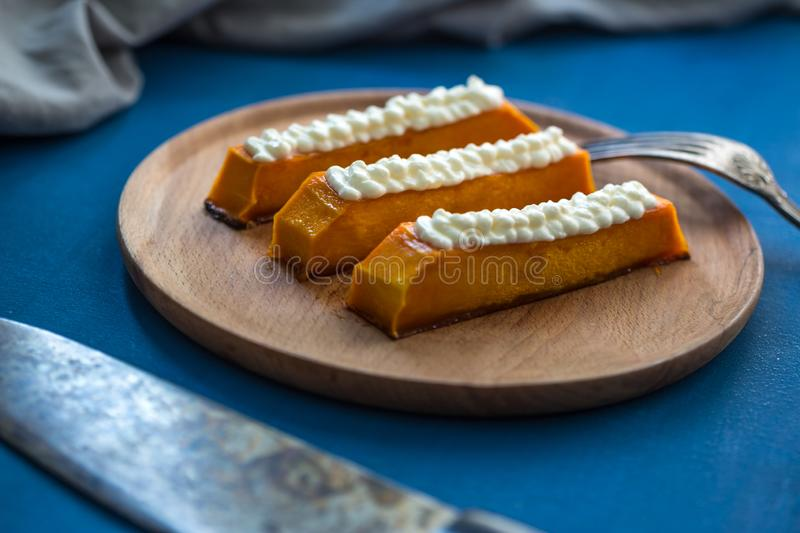 Sweet pumpkin dessert with cream cheese. Healthy tasty eastern food on the plate. sweet dessert with topping.  royalty free stock images