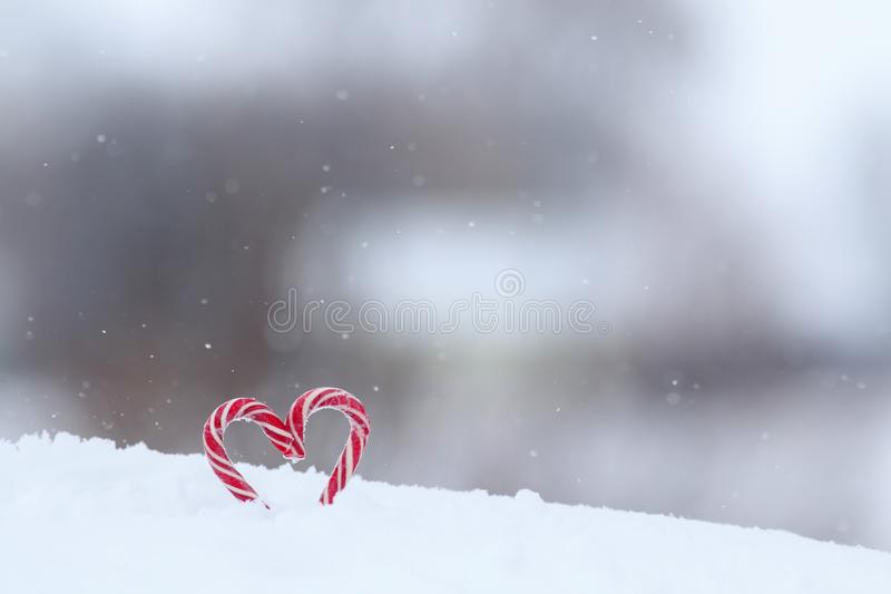 Sweet red candy lollipops heart shaped in white snow in festive Valentine`s day. Bright sweet red candy lollipops heart shaped in white snow in festive Valentine stock photography