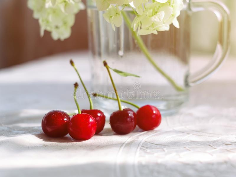 Sweet cherry berries on white tablecloth near a glass cup with flowers. Selective focus stock photography