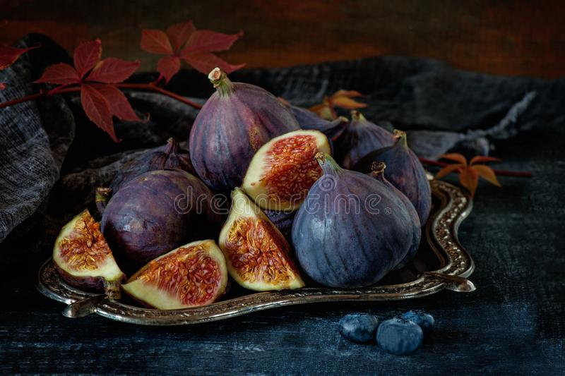 Sweet red ripe figs on a bunch of lies on a beautiful metal stand . stock photography