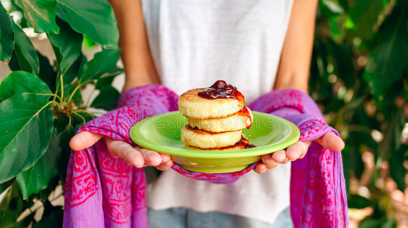 Sweet ricotta pancakes with jam in the woman's hands royalty free stock photography