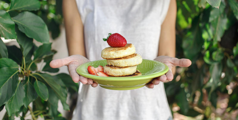 Sweet ricotta pancakes in woman hands royalty free stock photo