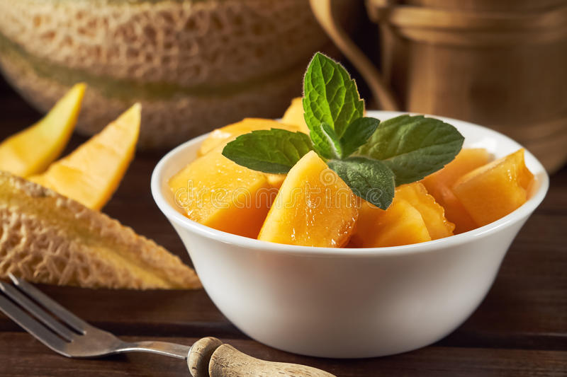 Sweet ripe cantaloupe. Melon cut and served with mint leaves stock photo