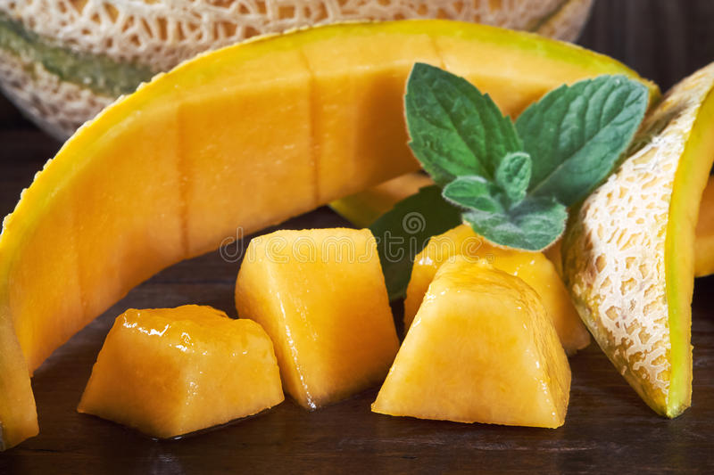 Sweet ripe cantaloupe. Melon pieces on wooden background royalty free stock image