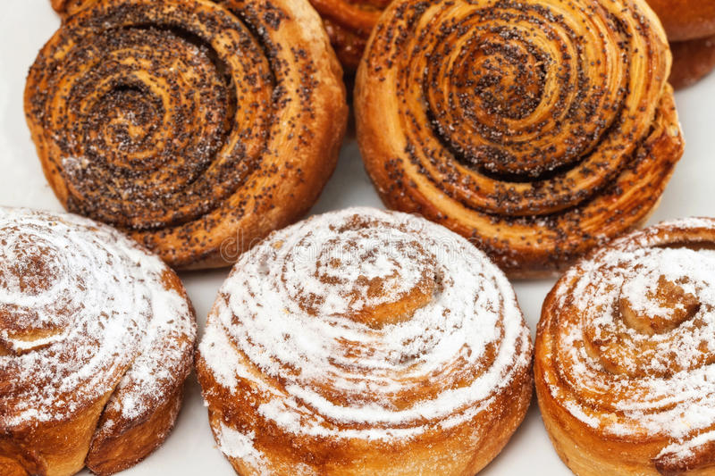 Sweet roll buns with shugar powder and poppy on table. Sweet roll buns with shugar powder and poppy on wooden table stock photos