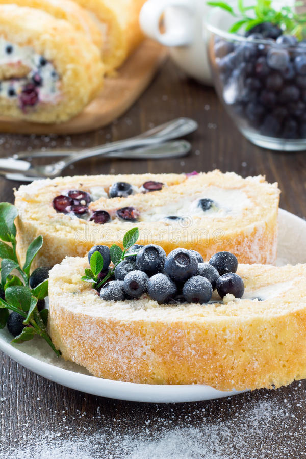 Sweet roll and a glass with fresh blueberry stock photography