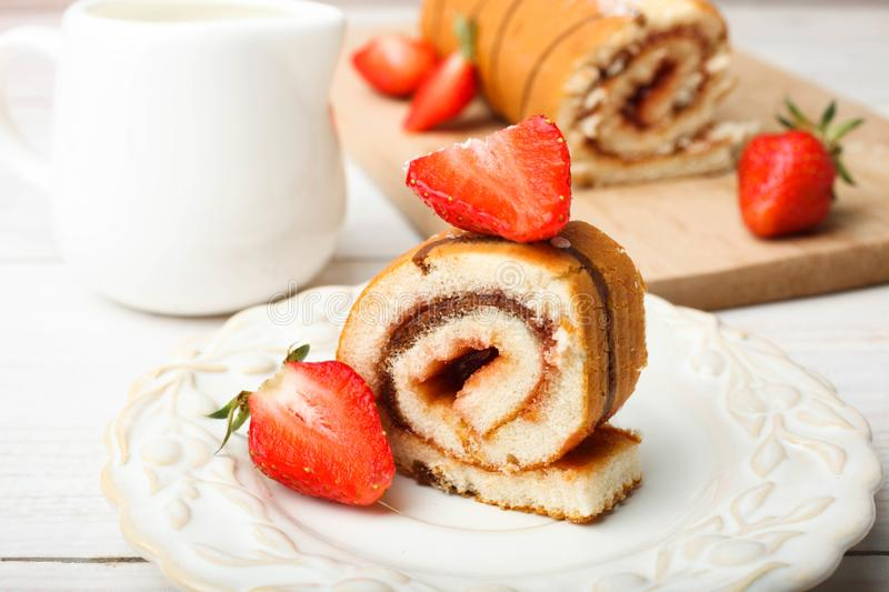 Sweet roll with strawberries. On plate and milk jug on wooden table on neutral background stock images