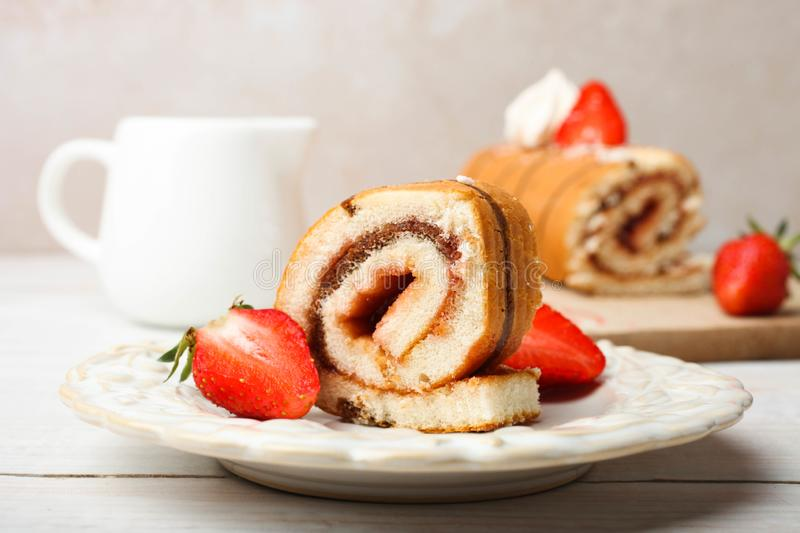 Sweet roll with strawberries. On plate and milk jug on wooden table on neutral background royalty free stock photos