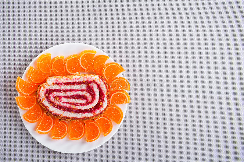 Sweet rolls, fruit. Tasty, colorful dessert: sweet rolls, orange marmalade on plate background table with tablecloth royalty free stock images