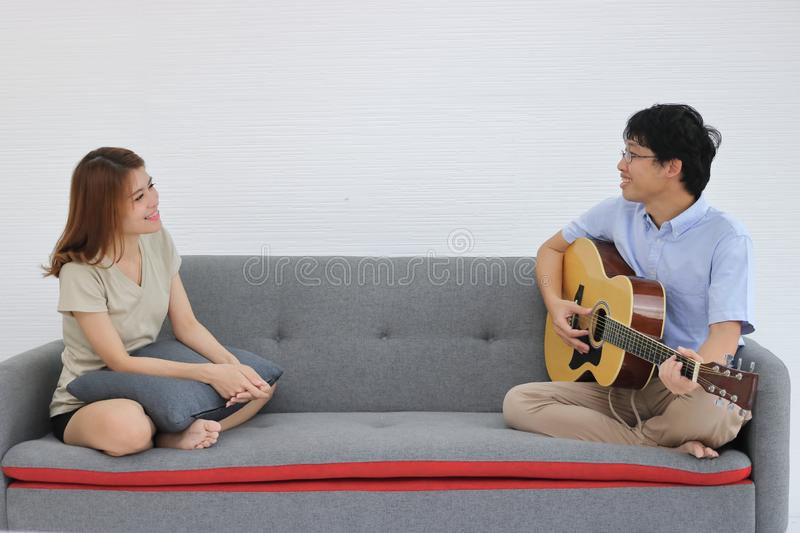 Sweet romantic young Asian couple playing acoustic guitar together in living room. Love and romance people concept royalty free stock photography
