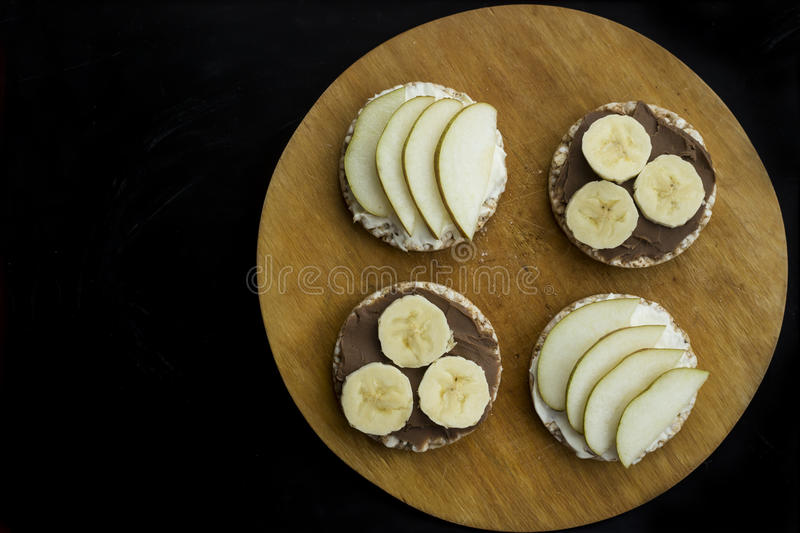 Sweet sandwiches with banana and peanut butter, cheese and pear on circular loaves buckwheat. top view stock images