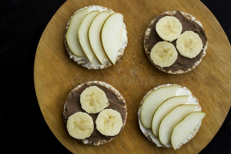 sweet sandwiches with banana and peanut butter, cheese and pear on circular loaves buckwheat. top view royalty free stock photography