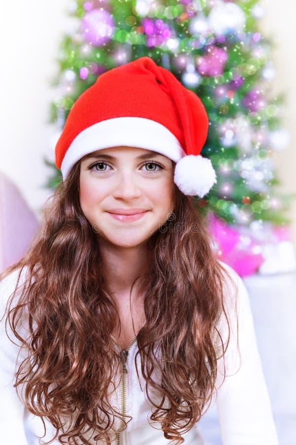 Sweet Santa girl near Christmas tree royalty free stock images