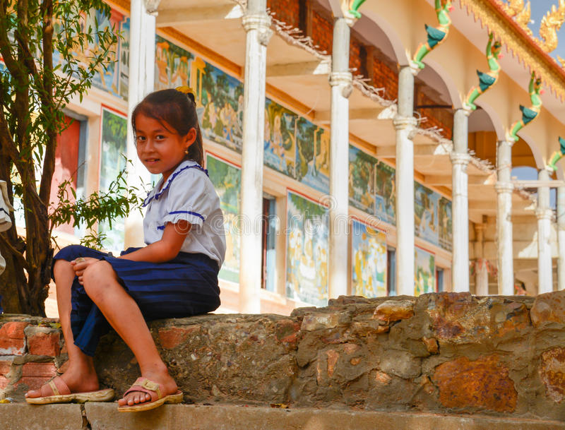 Sweet School Girl in Uniform Ouside Temple in Rural Cambodia. A sweet little girl sitting, in her school uniform, on steps outside of a colorful buddhist temple stock image