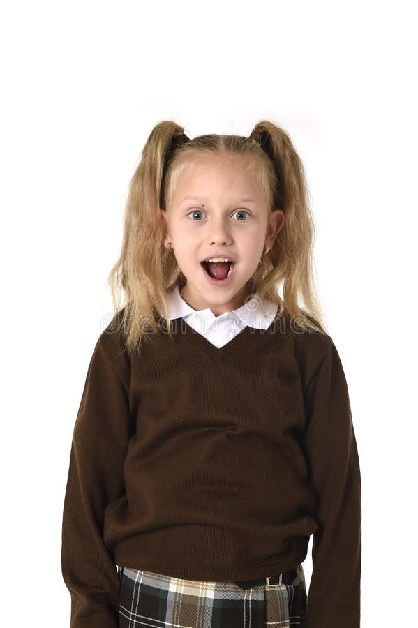 Sweet schoolgirl in pigtails and school uniform looking amazed shocked and surprised. Young beautiful and sweet schoolgirl in pigtails and school uniform looking royalty free stock photos