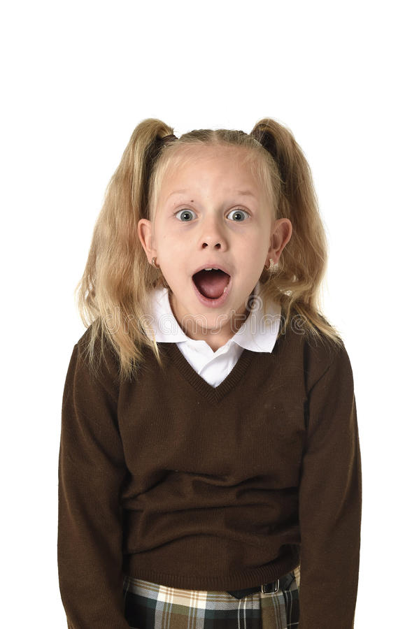 Sweet schoolgirl in pigtails and school uniform looking amazed shocked and surprised. Young beautiful and sweet schoolgirl in pigtails and school uniform looking stock photo