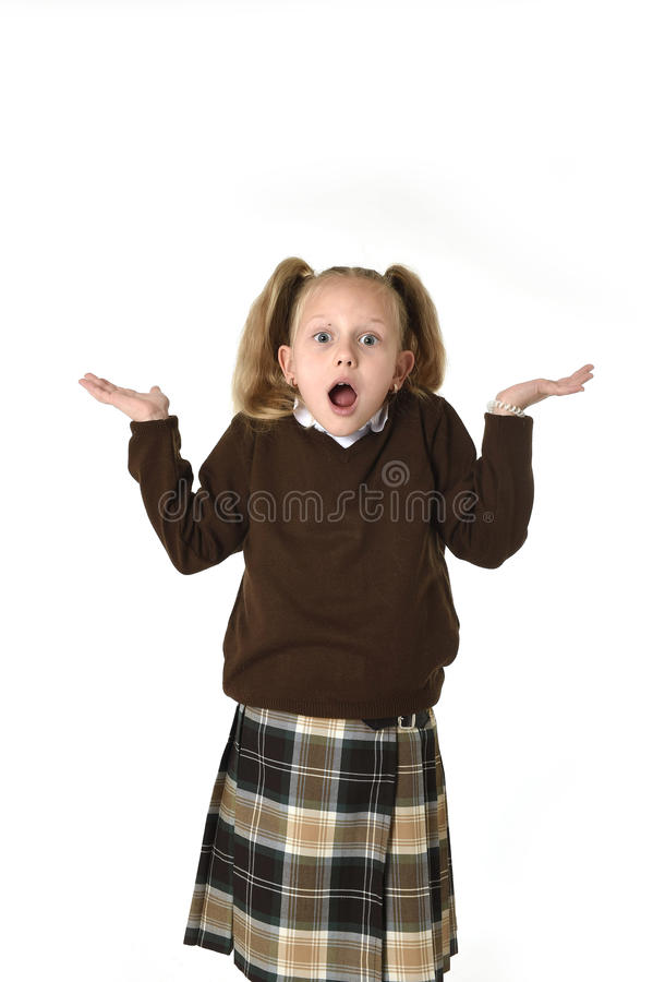Sweet schoolgirl in pigtails and school uniform looking amazed shocked and surprised. Young beautiful and sweet schoolgirl in pigtails and school uniform looking royalty free stock image