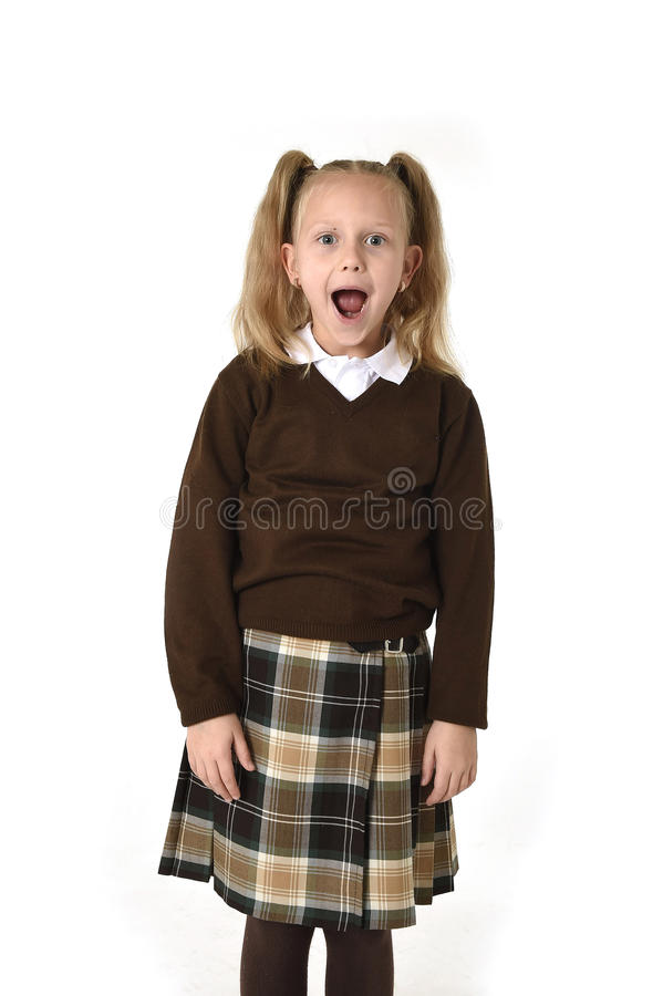 Sweet schoolgirl in pigtails and school uniform looking amazed shocked and surprised. Young beautiful and sweet schoolgirl in pigtails and school uniform looking stock photography
