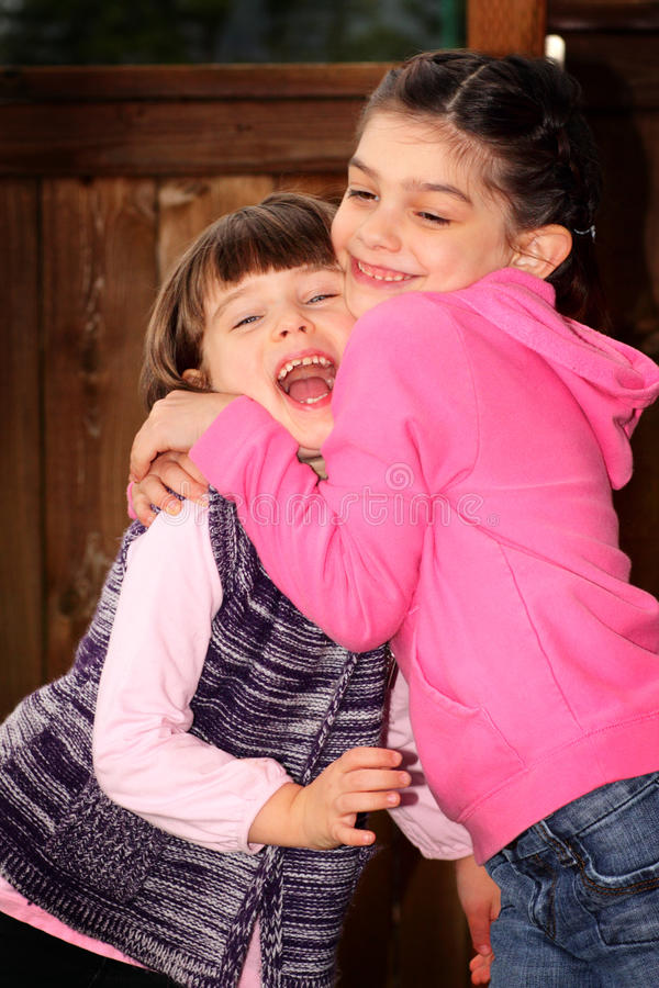 Sweet Sister Laugh. 2 little sweet dark haired elementary aged sisters loving each other with big laughs. Shallow depth of field royalty free stock images